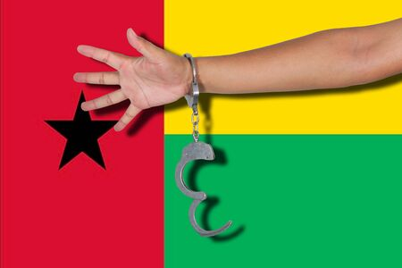 hand cuff: handcuffs with hand on Guinea Bissau flag