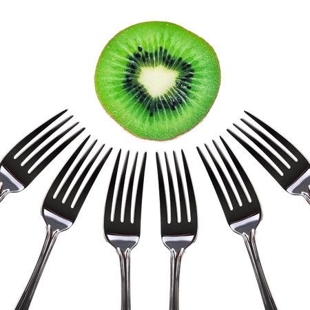 pierced: slice kiwi pierced on a many fork over white background