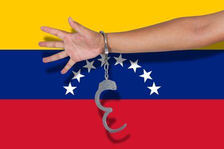 bandera de venezuela: handcuffs with hand on Venezuela flag Foto de archivo