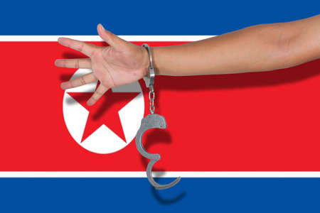 north korea: handcuffs with hand on North Korea flag