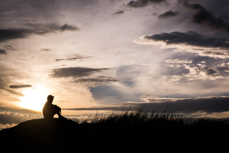 boy sitting: Sad boy silhouette worried on the meadow at sunset ,Silhouette concept