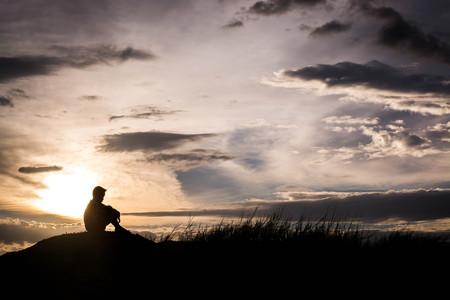 Smutny chłopiec sylwetka martwi na łące o zachodzie słońca, sylwetka koncepcja Zdjęcie Seryjne
