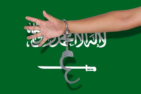 saudi arabia: handcuffs with hand on Saudi Arabia flag Stock Photo