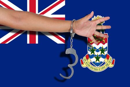 cayman islands: handcuffs with hand on Cayman Islands flag