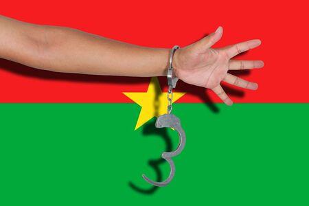 burkina faso: handcuffs with hand on Burkina Faso flag