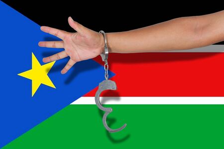 south sudan: handcuffs with hand on South Sudan flag