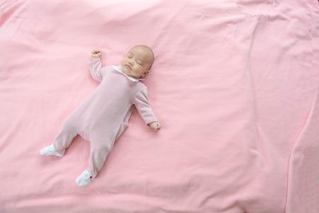 oversleep: Sleeping baby on pink background Stock Photo