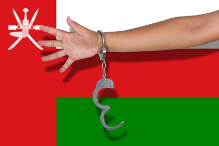 oman: handcuffs with hand on Oman flag Stock Photo