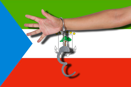 equatorial guinea: handcuffs with hand on Equatorial Guinea flag