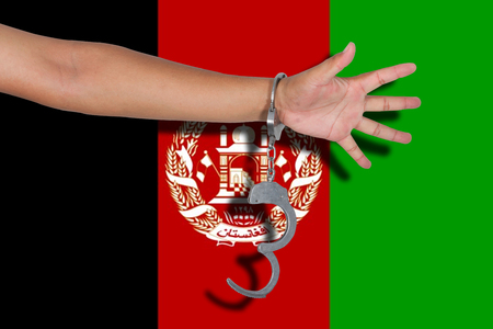 afghanistan flag: handcuffs with hand on Afghanistan flag