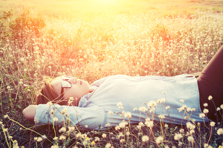 beatitude: Happy hipster woman lying down on dandelion field close her eyes feeling comfortable