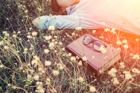beatitude: young woman napping on the dandelion field after reading book put out glasses on the book