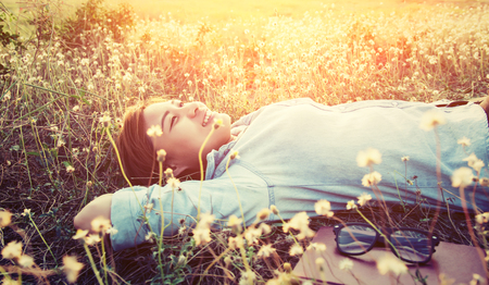 beatitude: Beautiful young hipster laying down on the dandelion field smiley into the sky Stock Photo