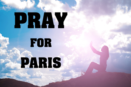 shootings: Silhouette of woman praying over beautiful sky with text Pray for Paris