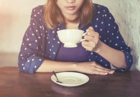 gaffe: beautiful woman hands with coffee cup on a wood table