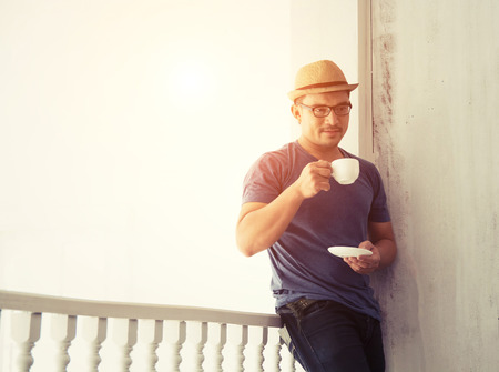 lean out: Handsome man standing out of home lean on the balcony drinking coffee in the morning