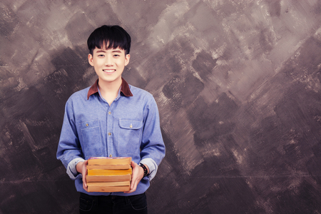 man holding book: Handsome young asian man holding book on the grunge wall smiley looking at camera