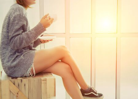 wooden chair: Young woman  holding a cup of coffee and sitting on wooden chair near the window in the morning Stock Photo