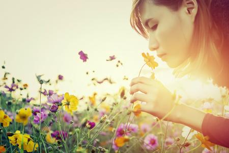 Mooie jonge vrouw ruiken de bloemen