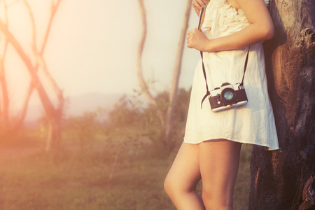 photography: Vintage of beautiful women photography standing hand holding retro camera with sunrise