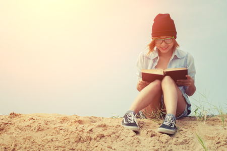 happy young woman: Young girl reading book and sitting on the beach with sunrise Stock Photo
