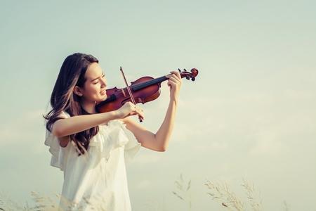美しい女性立っている草原のバイオリンの演奏 写真素材