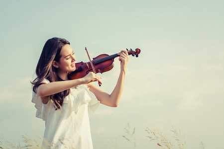 Beautiful Woman standing Playing the violin in the meadow