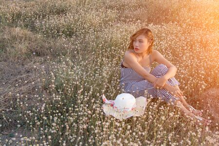 sadly: Sexy Beautiful woman sitting in flower field sadly and loneliness Stock Photo