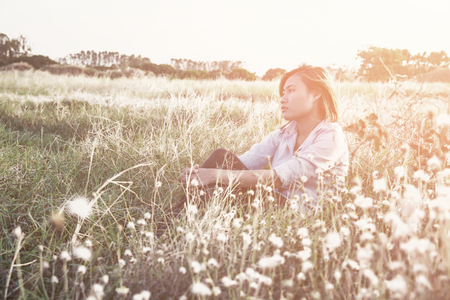 luxuriate: Young beautiful hipster pensive woman sitting on the meadows