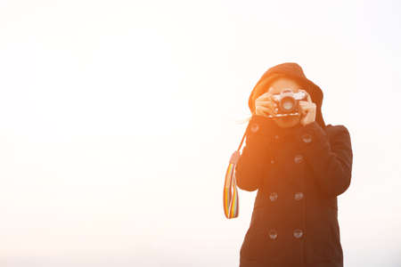 Young woman wearing black coat standing carry retro camera Stock Photo