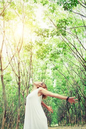 女性のライフ スタイルのコンセプト: 若いアジア女性は、森の新鮮な空気見てとても快適で彼女の手を伸ばす