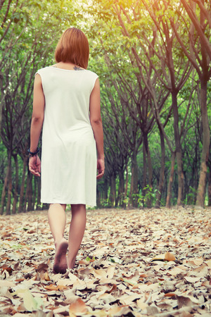 uncluttered: Sad woman walking alone in the forest feeling sad and lonely