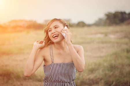 sexy woman standing: Beautiful sexy woman standing talking on phone in the grass field look so happy
