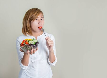 sparingly: Beautiful young woman using fork to eat a tomato in bowl of salad with gusto.