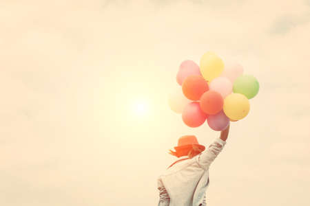 sky brunch: Young woman wearing hat holding colorful of balloon near seaside on the summer Stock Photo