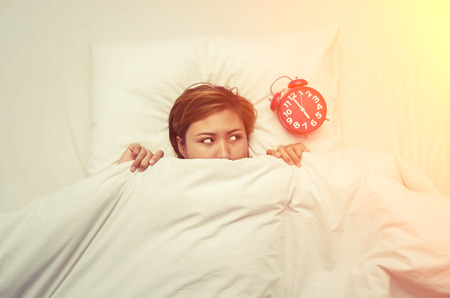 oversleep: Young woman lying on the bed looking at the alarm clock in the morning