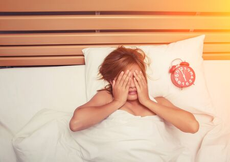 hands off: beautiful young woman take hands off her face on the bed in the morning when alarm clock is ringing dont want to wake up Stock Photo