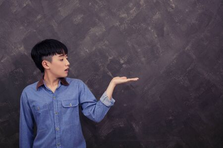 young man standing: handsome young man standing against grunge background look at his left hands surprise
