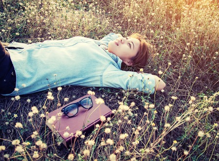 pacification: Beautiful young hipster laying down on the meadows field smiley