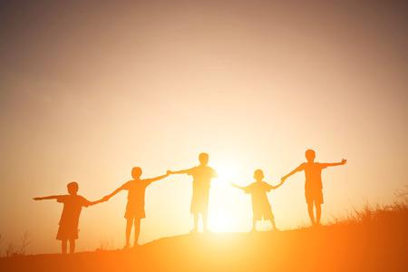 Het silhouet van kinderen die spelen op de zomer zonsondergang gelukkige tijd