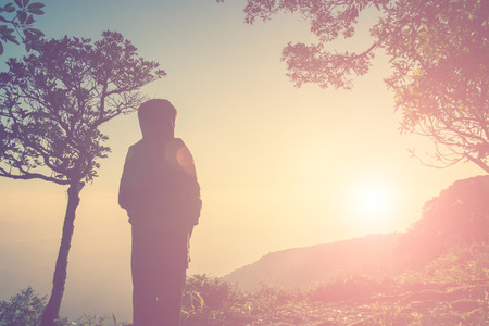 trouble free: Silhouette of woman standing on top of the mountain waiting someone Stock Photo