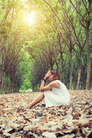 self worth: Sad woman hands off her face so sadly sitting on dry leaf in the forest
