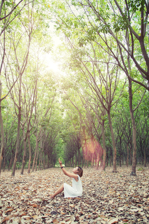 humbled: beautiful young woman pray for something in the green forest Stock Photo