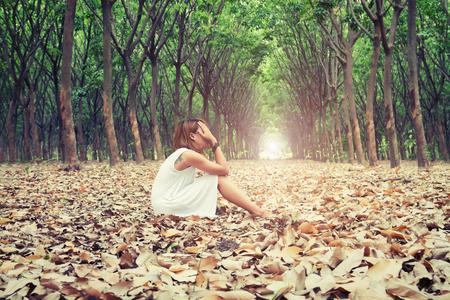 悲しそうに森の中の枯葉の上に座って顔を悲しい女性手 写真素材