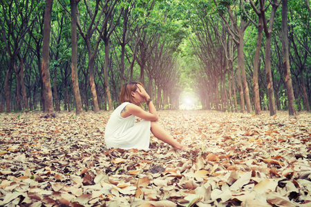 Droevige vrouw handen van haar gezicht zo helaas zitten op droog blad in het bos