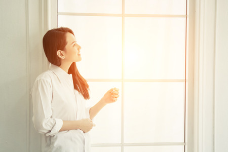 Young beautiful woman standing against window watching at sunrise in the morning.
