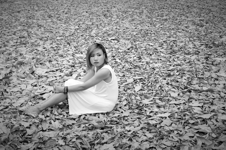 sadly: Young asian woman sadly sitting on dry leaf in the forest alone