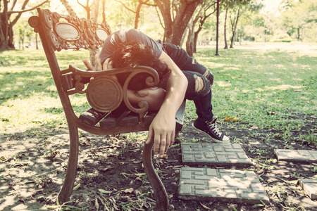 during the day: Young man sleeping on bench outdoor in city park during day