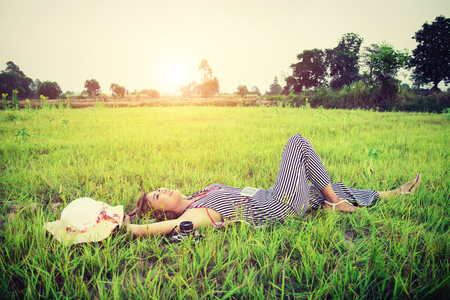 down beat: Young beautiful woman listening to music while lying down on green grass