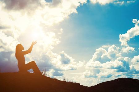 Silhouette der Frau, die über schönen Sonnenaufgang Hintergrund beten Standard-Bild - 57338153